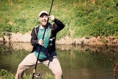 成功渔,有钓鱼竿的人 滑稽,乐趣 库存照片