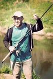 成功渔,有钓鱼竿的人 滑稽,乐趣 免版税图库摄影