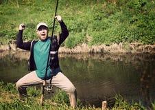 成功渔,有钓鱼竿的人 滑稽,乐趣 免版税库存照片