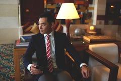 年轻成功的亚洲商人在拿着手机的礼服穿戴了,当坐在现代办公室时 图库摄影
