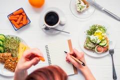 成功的人民早晨习性  天计划和健康膳食 吃红萝卜和写在笔记本的妇女在服务为 免版税库存照片