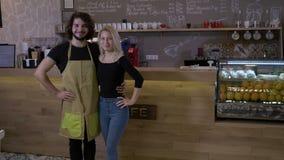 成功的企业家小企业主骄傲地站立和愉快在咖啡店微笑- 股票录像