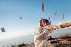 成功的兴旺的自由职业者在天空中的投她的金钱 免版税库存图片