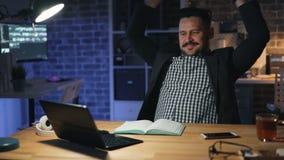成功的商人与膝上型计算机一起使用在办公室在夜放松的微笑 股票录像