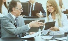 成功的商人和他的助理在一种好心情谈论工作计划 库存照片