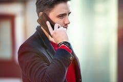 成功的商人走和谈话在城市街道上的电话 库存照片