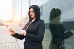 成功的女商人与在一个城市布局的片剂一起使用 库存照片