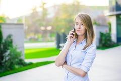 成功的女实业家或企业家谈话在手机,当走室外时 图库摄影