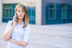 成功的女实业家或企业家谈话在手机,当走室外时 免版税库存图片