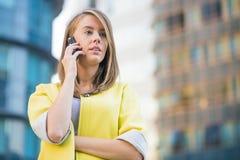 成功的女实业家或企业家谈话在站立在他的办公室前面的手机 免版税库存图片