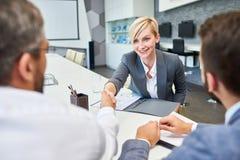 成功的女实业家问候伙伴在证券交易经纪人行情室 免版税图库摄影