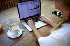 年轻成功的女性自由职业者用途网书后面看法距离工作的在她的休闲时间 库存照片