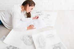 成功的妇女艺术家图画在车间 免版税图库摄影
