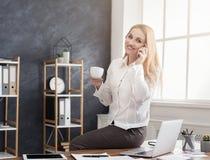 成功的妇女谈话在电话和饮用的咖啡 库存照片