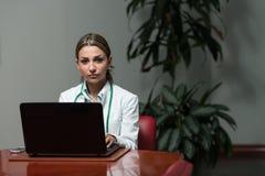 成功的妇女医生Working At Laptop 免版税图库摄影