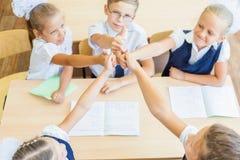 成功的小组孩子在有赞许姿态的学校 免版税库存图片