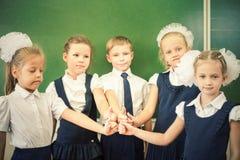 成功的小组孩子在有赞许姿态的学校 库存图片