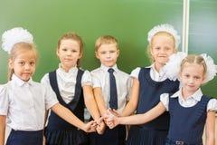 成功的小组孩子在有赞许姿态的学校 免版税库存照片