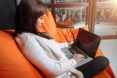 成功的少妇坐沙发在办公室,研究她的膝上型计算机 免版税库存图片