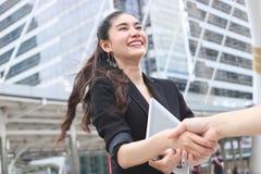 成功的年轻亚裔握手的女商人和人在成交以后 概念另外现有量合伙企业编结难题二 库存照片