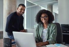 成功的年轻企业同事画象在办公室 免版税库存图片