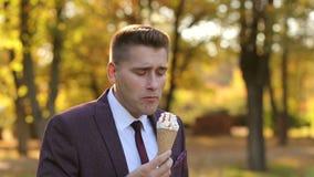 成功的年轻商人在秋天公园走并且吃冰淇淋 影视素材
