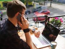 成功的年轻商人画象讲话由电话,当工作在咖啡馆户外时 库存照片