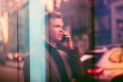 成功的年轻成人商人谈话的窗口反射在手机的在城市街道上 库存照片