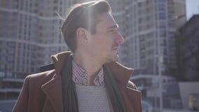 成功的微笑的帅哥画象棕色外套身分的在看城市的街道  高大厦 股票视频