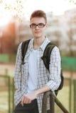 成功的微笑的年轻学生画象戴眼镜的 免版税库存图片