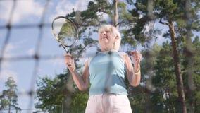 成功的快乐的愉快的成熟妇女在网球赛中获胜 跳跃的老妇人举手与球拍 股票录像