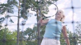 成功的愉快的成熟妇女在网球赛中获胜 跳跃的老妇人举手与在a的球拍 影视素材