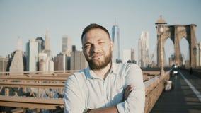 成功的愉快的白种人商人横穿胳膊画象,微笑对照相机在布鲁克林大桥,纽约4K 股票录像
