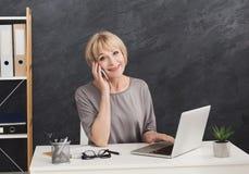成功的成熟企业家谈话在电话 免版税库存照片