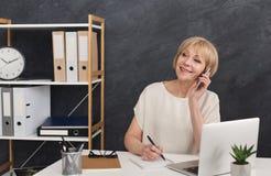 成功的成熟企业家谈话在电话 免版税库存图片