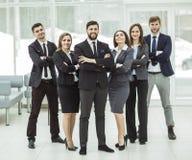 成功的概念在事务的:紧挨着站立一个坚实企业的队和胳膊在他前面横渡了 库存图片
