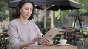成功的网络购物通过片剂通过老妇人坐室外 股票录像