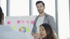 成功的英俊的聪明的亚洲创造性的对他的同事的商人当前创造性的工作候选会议地点的在办公室 股票录像