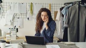 成功的裁缝企业家在手机谈话并且使用膝上型计算机 妇女从纺织品的忙于预定的织品 股票视频