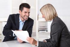 成功的配合:坐在书桌talki的商人和妇女 免版税库存照片