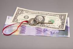 成功的钥匙与在一个美国人美元和1000 Swi的红色弓 库存照片