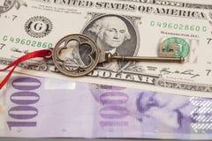 成功的钥匙与在一个美国人美元和1000 Swi的红色弓 免版税库存照片