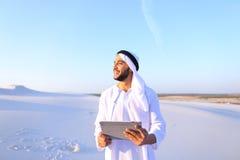 成功的阿拉伯商人在手上举行并且使用片剂, s 图库摄影