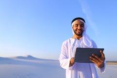 成功的阿拉伯商人在手上举行并且使用片剂, s 免版税库存图片