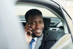 成功的非洲商人说在汽车的电话里 库存图片