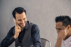 成功的项目 formalwear的微笑两个快乐的商人谈论某事和,当他们中的一个指向数字式时 免版税图库摄影