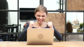 成功的兴奋由研究膝上型计算机的女孩的,正面图 股票录像