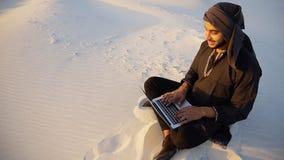 成功的Emirati商人读经营计划并且坐w 库存照片