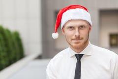 成功红色头和有胡子的商人画象在圣诞老人帽子 查看照相机和微笑 库存照片