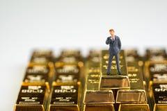 成功财富管理概念,微型图商人身分在堆与拷贝空间的发光的金制马上的齿龈金块锭 免版税库存图片